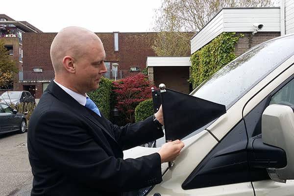 Facilitair medewerker Marcel Hessing illustreert de betekenis van de vlaggetjes op de overbrengauto