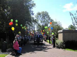 Uitvaartverzorger Riemond gaat het uitvaartbusje voor door een haag van ballonnen