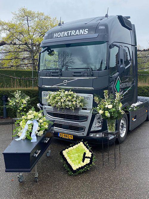 Hoektrans-truck en uitvaartkist Jan Galdon met prachtige bloemen opgesteld voor het Dunweg Uitvaartcentrum