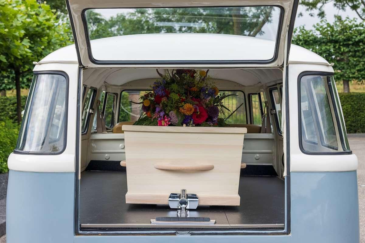Kist met bloemen in het Volkswagenbusje - bijzonder rouwvervoer